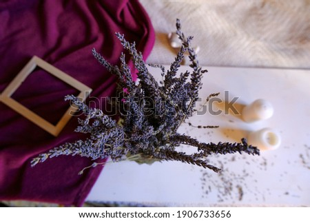bunch of lavender in glass vase on a white background across picture frame, purple blanket, candles. Top view. Home decor. interior design