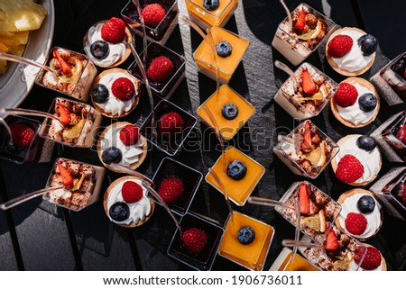 Desserts, snacks, quick dessert, small sweets, fruits, raspberries, strawberries, starfruit, cream, marshmallows, mango, mousse dessert, pineapple, blackberry, buffet and service, outdoor service.  Royalty-Free Stock Photo #1906736011