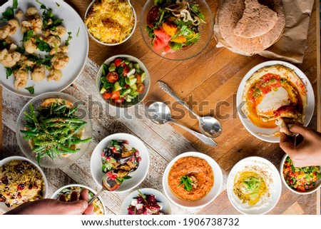 Mediterranean dips and spreads. Traditional classic Turkish and Greek cuisines. Hummus, Tzatziki served with pita bread and mezze.  Royalty-Free Stock Photo #1906738732