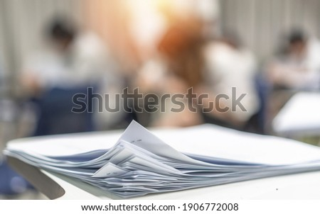 Exam answer sheet pile, blurry application document paperwork stack on office work table in examination room or classroom with blur education background school class university students taking test Royalty-Free Stock Photo #1906772008
