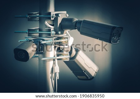 Three Modern Security Megapixel CCTV Cameras Installed on Aluminium Outdoor Pole. Closed Caption Television Technologies.