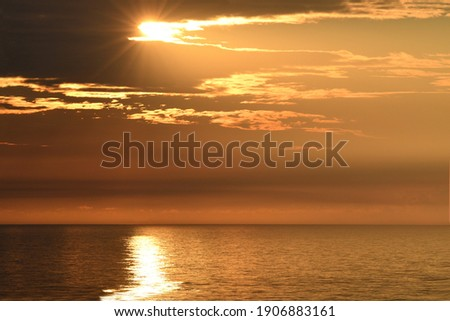 A high angle point of view from the balcony of an Atlantic city hotel captures the sun break the horizon and present with a beautiful sunrise off the Atlantic ocean. Royalty-Free Stock Photo #1906883161