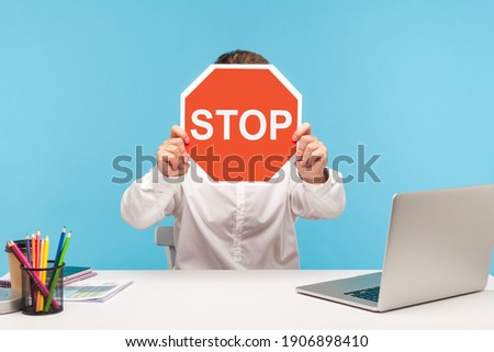 Man office worker in white shirt hiding face behind red stop traffic sign, sitting at workplace with laptop, symbol of prohibition restriction. Indoor studio shot isolated on blue background