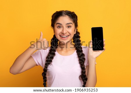 I Recommend. Portrait of excited young indian woman holding smartphone with black blank screen in hand, showing device and thumbs up sign gesture. Gadget with empty free space for mock up