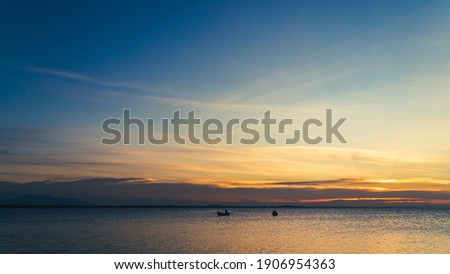 Dusk sky over sea in the evening on twilight with colorful sunlight Royalty-Free Stock Photo #1906954363