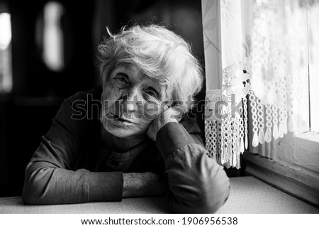 The old lady is sitting at the kitchen table. Black and white photo.