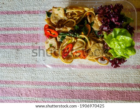 """Above picture of """"Pad Kee Mao"""" spaghetti with chicken, pork in a box for sale. Placed on the table with the old tablecloth ready to serve the customer That looks delicious"""
