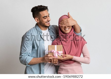 Surprise for you. Romantic arab man covering eyes of his muslim wife with hand and giving present, greeting her with birthday, wedding anniversary or valentines day, standing on grey studio background