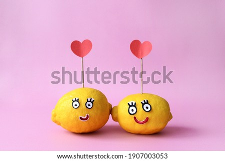 Loving cartoon couple of yellow lemons with hearts on a pink background. Valentine's card.