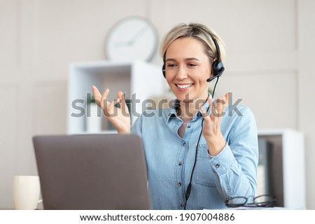 Millennial teacher giving online lesson on webcam from home, blogger broadcasting on air. Young tutor in headphones participating in educational or business web conference on laptop Royalty-Free Stock Photo #1907004886