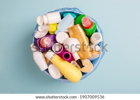 separate collection of sorted HDPE bottles from cosmetics and detergents in bucket for recycling. High-Density Polyethylene recyclable bottles on blue background. Plastic garbage. Save the plane Royalty-Free Stock Photo #1907009536