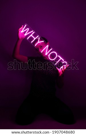 Beautiful young girl holding pink neon sign why not?. Trendy style. Neon sign. Custom neon. Home decor.