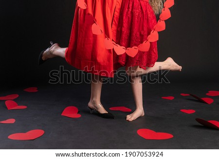 Together, mother and daughter hold garlands of red Valentine's hearts symbol, Valentine's board, romantic hearts on the floor. . day, black in red dress girl, barefoot