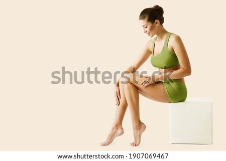 Body Leg Beauty Woman. Natural Skin Care Green Treatment. Slim Model applying depilation Cream. Body Spa Massage Royalty-Free Stock Photo #1907069467