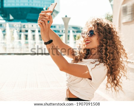 Beautiful smiling model with afro curls hairstyle dressed in summer hipster clothes.Sexy carefree model posing in the street in sunglasses.Taking selfie self portrait photos on smartphone