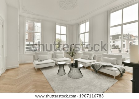 Living room with large windows, white carpet and comfortable sofas Royalty-Free Stock Photo #1907116783