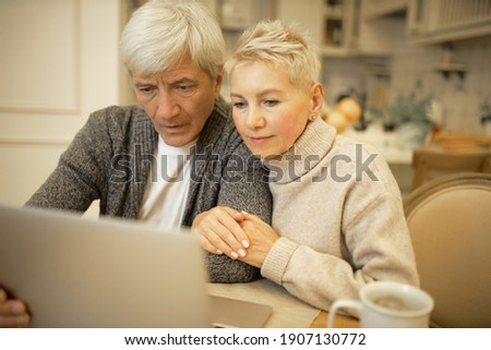 Serious elderly man and his blonde wife sitting in kitchen in front of open laptop, surfing internet together, signing up on website or social networks, looking at screen with concentrated expression