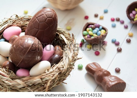 Chocolate eggs and easter almonds on bird nest, chocolate bunny and sweets on white wooden table Royalty-Free Stock Photo #1907143132