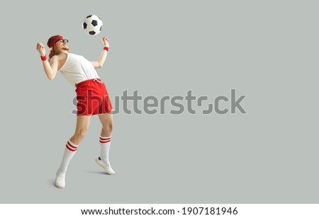 Funny nerdy man having fun with a football. Happy young male sports fan in white and red sportswear kicking away soccer ball on light gray background with free space for advertising text