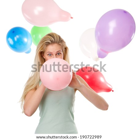 Close up portrait of a beautiful young woman blowing up balloons for a party #190722989