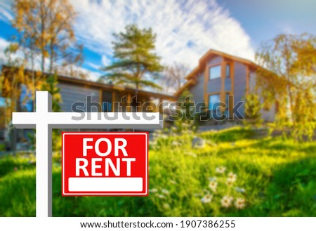For rent sign next to a large house. For rent sign as a symbol of private property renting. for rent sign on a red background. Concept - rental a private  house. Renting a country house. Royalty-Free Stock Photo #1907386255