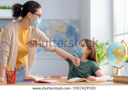 Back to school. Happy children are wearing facemasks sitting at desks. Girls with teacher in classroom. Royalty-Free Stock Photo #1907429920