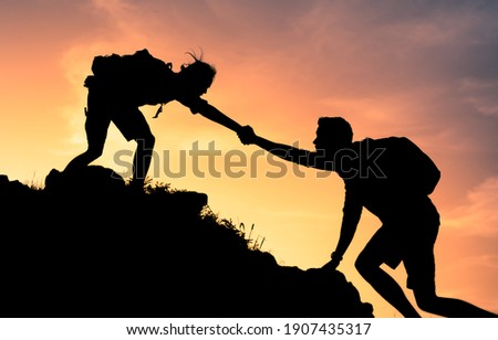 Two climbers helping each other up edge of a mountain. Teamwork, and physical and mental strength concept.  Royalty-Free Stock Photo #1907435317