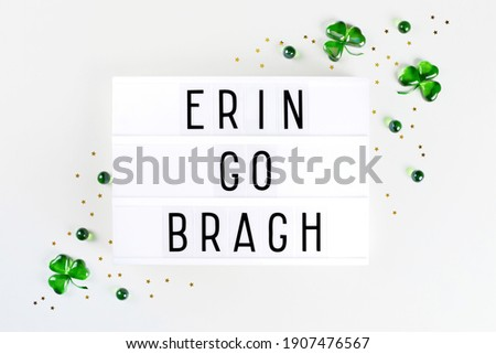 Lightbox with text Ireland forever written in Irish and shamrock symbols made of green hearts and stars confetti on white background. Flat lay Irish holiday card Spring 17 march lucky clover design.