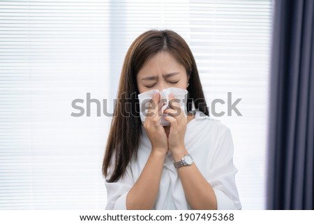 Asian woman sneezes at home. She uses a tissue to cover her mouth. Royalty-Free Stock Photo #1907495368