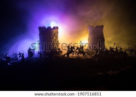 Medieval battle scene. Silhouettes of figures as separate objects, fight between warriors at night. Creative artwork decoration. Foggy background. Selective focus Royalty-Free Stock Photo #1907516851
