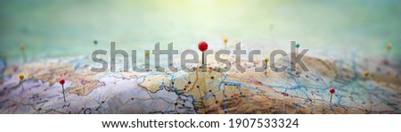 Pins on geographic map curved like mountains. Pinning a location on map with mountains. Adventure, discovery, navigation, geography, mountaineering, rock climbing, hike  and travel concept background. Royalty-Free Stock Photo #1907533324
