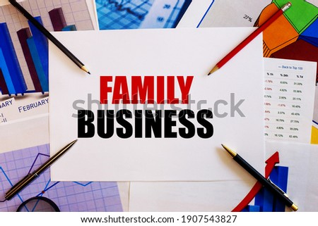 The word FAMILY BUSINESS is written on a white background near colored graphs, pens and pencils. Business concept
