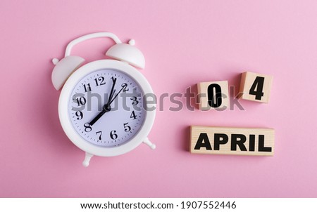 On a pink background, a white alarm clock and wooden cubes with the date of APRIL 04 Royalty-Free Stock Photo #1907552446