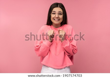 Photo of attractive young woman in glasses waits impatiently, looks forward. Wears casual pink t-shirt isolated pink color background