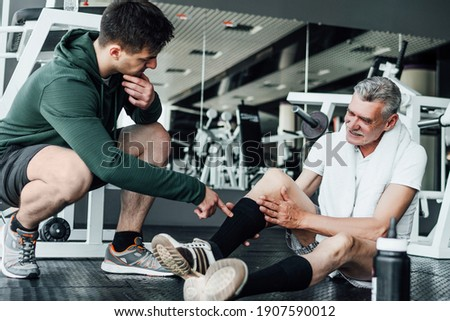 In the photo, two people in the gym, one of them on the floor with an injured leg, a rehabilitation coach helps him. Royalty-Free Stock Photo #1907590012