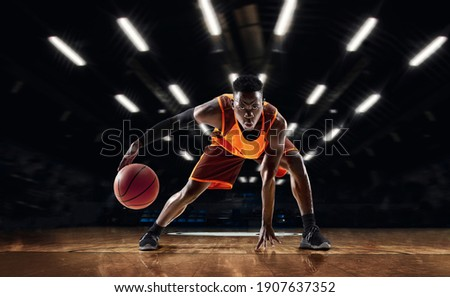Ready to jump. African-american young basketball player in action and motion in flashlights over dark gym background. Concept of sport, movement, energy and dynamic, healthy lifestyle. Arena's drawned Royalty-Free Stock Photo #1907637352
