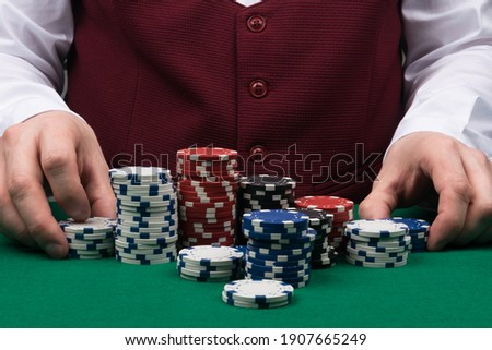 the croupier at the green poker table is sorting out the poker chips