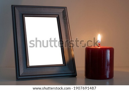 Red funeral candle next to a blank wood photo frame