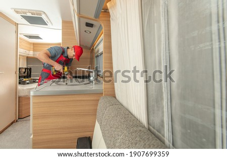 Recreational Vehicles Caucasian RV Technician in His 40s Repair Modern Travel Trailer Stove. RV Appliances Industry. Royalty-Free Stock Photo #1907699359