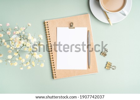 Top view blank paper Notebook, flowers, golden paper binder clips, cup of coffee and pen. Desktop mock up, Flat lay of green working table background with office equipment, mockup greeting card Royalty-Free Stock Photo #1907742037