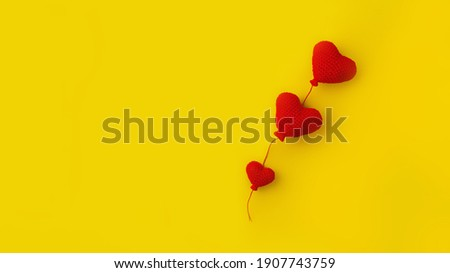 three knitted red heart-shaped balloons in row on yellow background, concept of love, banner
