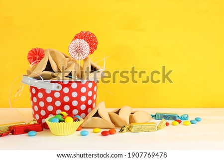 Purim celebration concept (jewish carnival holiday). Hamantaschen cookies and sweets over wooden table