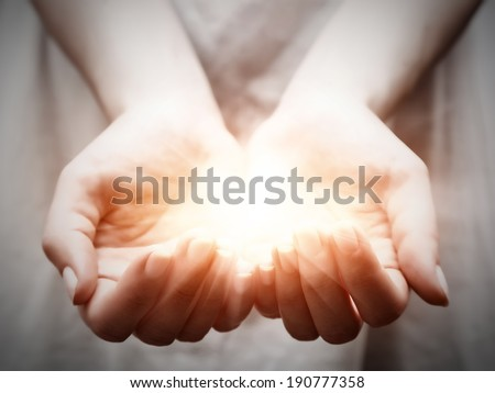 The light in young woman hands in cupped shape. Concepts of sharing, giving, offering, taking care, protection Royalty-Free Stock Photo #190777358