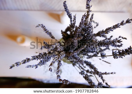 bunch of lavender in glass vase on a white background across picture frame, white blanket, candles. Top view. Home decor. interior design