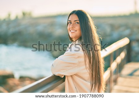 Young hispanic girl smiling happy leaning on the balustrade.