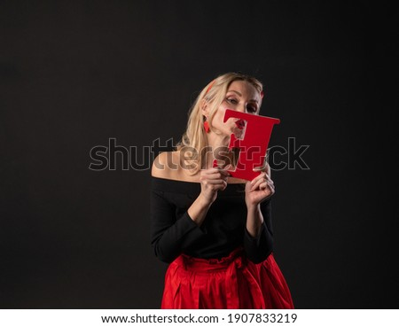 The girl holds the letters of the word LOVE love symbol, Valentine's board, on the floor hearts romance romance. shape. emotion forever, gift in a red dress girl, barefoot