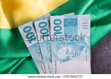 One hundred reais notes on Brazilian flag. Royalty-Free Stock Photo #1907846737