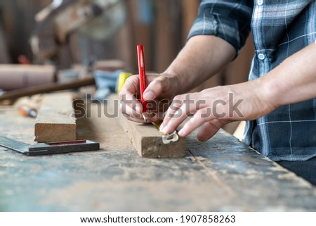 Male carpenter using pencil drawing sign on plank. Craftsman doing his job at the carpentry workshop