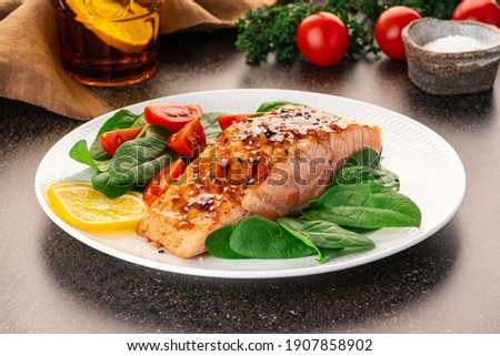 Baked or fried salmon and salad, Paleo, keto, fodmap, dash diet. Mediterranean food with steamed fish. Oven asian dish with teriyaki. Healthy concept, gluten free, lectine free, side view Royalty-Free Stock Photo #1907858902