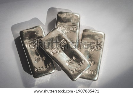Four cast silver bars on a gray background. feinsilber is fine silver. Royalty-Free Stock Photo #1907885491